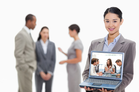 Glad businesswoman talking to her team against businesswoman smiling showing a laptop screen with coworkers in the background photo
