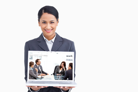Thoughtful businesswoman talking to her team during a meeting against close up of smiling saleswoman presenting laptop screen photo