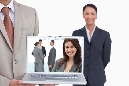 Happy businesswoman posing while her team discussing against laptop being presented by salesman with colleague behind him photo