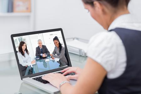 mujeres juntas: director sonriente sentado en el escritorio frente a la ventana entre dos empleados contra los trabajadores de negocios usando la computadora portátil en el escritorio