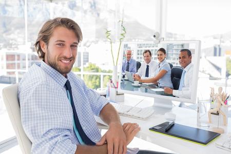 reuniones empresariales: La gente de negocios de intercambio de ideas en contra sonriendo diseñador sentado en su escritorio