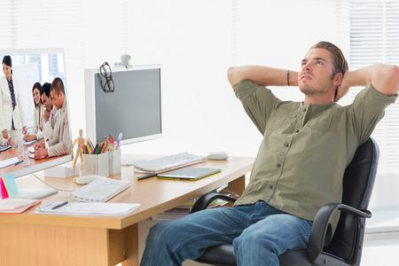 charismatic: Charismatic businesswoman doing a presentation against handsome designer leaning back at his desk