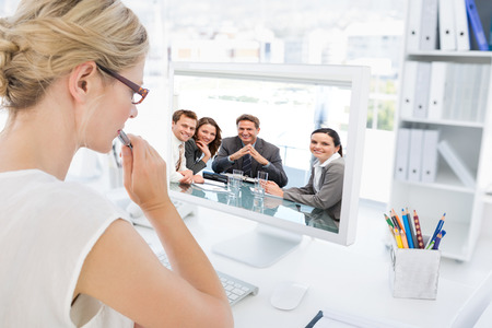 Portrait of a positive manager with his team against rear view of a female photo editor working on computer photo