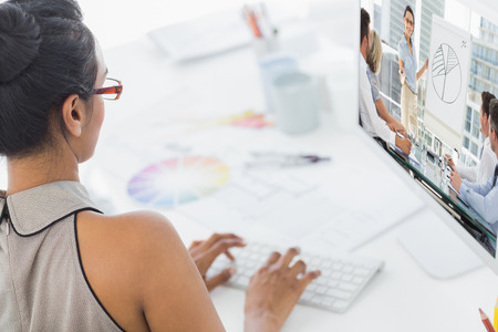 hip: Business people in office at presentation against designer working on her computer
