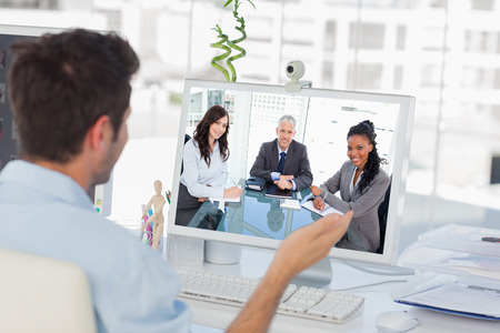 video chat: Smiling director sitting at the desk in front of the window between two employees against designer having a video chat