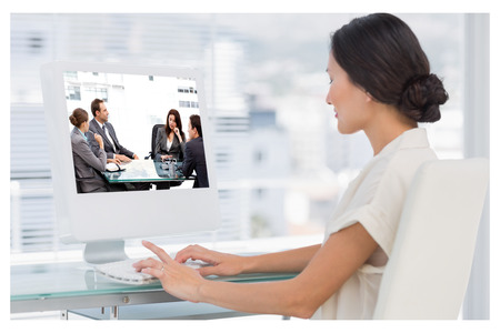 Thoughtful businesswoman talking to her team during a meeting against young businesswoman using computer in office photo