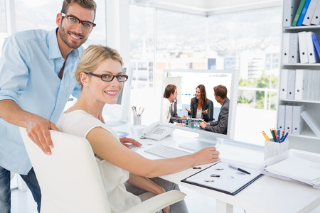 Attractive businesswoman laughing with her team against side view portrait of photo editors working on computer photo