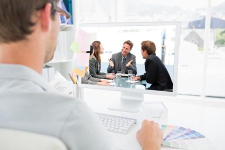 Une équipe heureuse rire ensemble à une réunion contre la vue arrière de éditeur de photos travaillant sur ordinateur Banque d'images - 38064076
