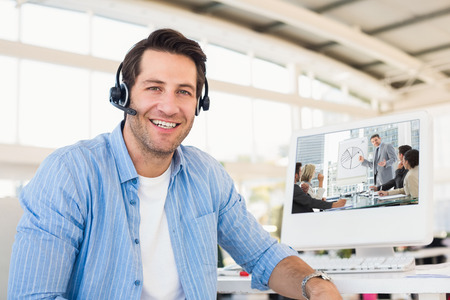 Business people in office at presentation against portrait of a smiling photo editor wearing a headset Foto de archivo