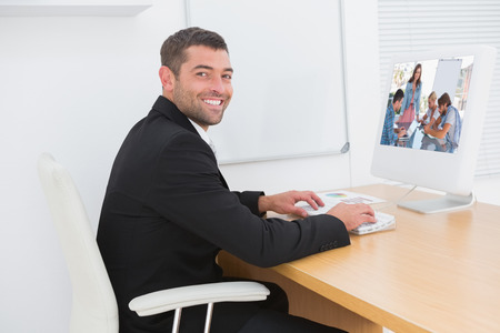 one on one meeting: Team having meeting with one woman smiling at camera against smiling businessman working at a desk