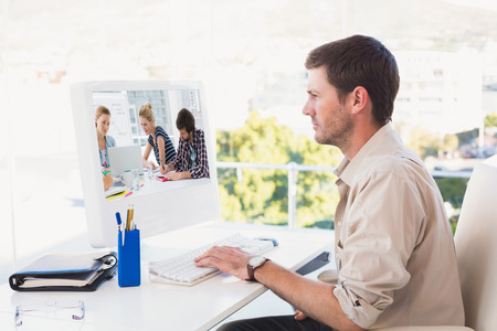 Casual business people around conference table in office against casual businessman working at his desk photo