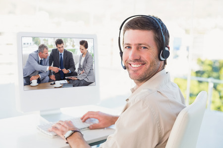 Work team having a meeting together against businessman in headset smiling at camera photo