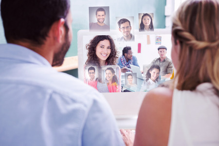 Colleagues looking at computer against smiling woman with creative team working behind photo