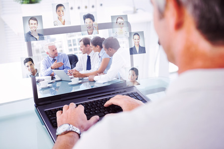 Man with grey hair typing on laptop against group of business people brainstorming together photo