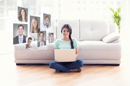 Pretty girl sitting on floor using laptop smiling at camera against profile pictures photo