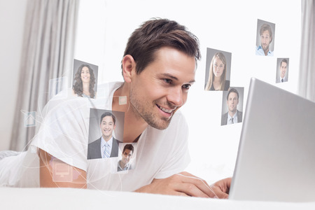 Relaxed casual man using laptop in bed against profile pictures photo