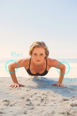 plank position: Fit blonde in plank position on the beach against fitness interface Stock Photo