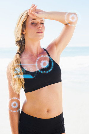 forehead: Fit blonde wiping her forehead on the beach against fitness interface