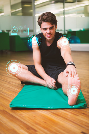 touching toes: Fit smiling man warming up in fitness studio against fitness interface