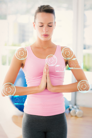 manos unidas: Woman with joined hands and eyes closed at fitness studio against fitness interface