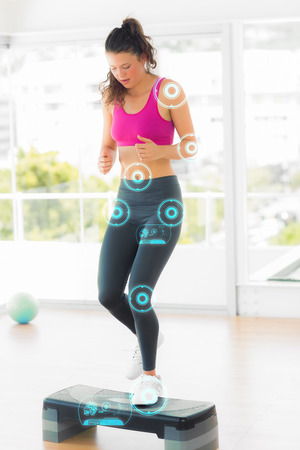 woman looking down: Full length of a fit woman performing step aerobics exercise against fitness interface