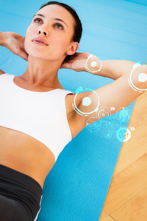 crunches: Determined young woman doing abdominal crunches against fitness interface