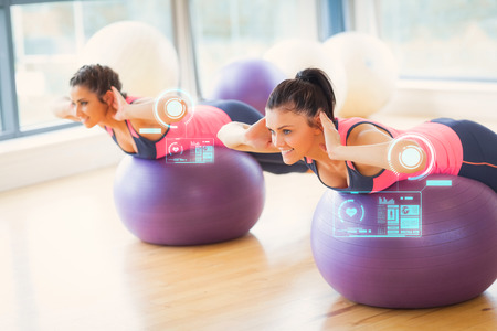 Two fit women exercising on fitness balls in gym against fitness interface photo