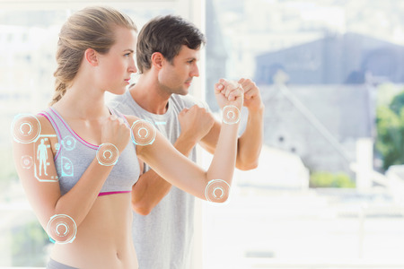 stance: Serious couple standing in boxing stance in fitness studio against fitness interface