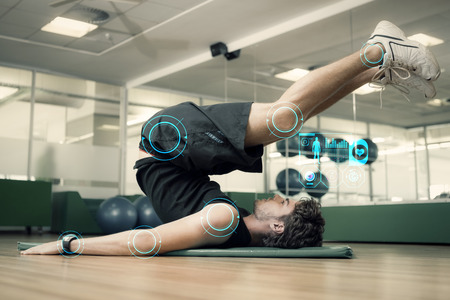 fitness men: Hombre apto que hace pilates en estudio de la aptitud contra interfaz de fitness