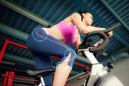 Determined young woman working out at spinning class against fitness interface Banco de Imagens