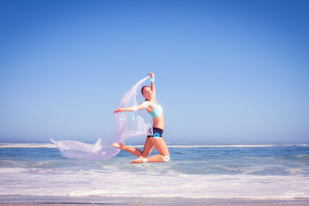 scarf beach: Fit woman jumping gracefully on the beach with scarf against fitness interface