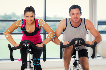 working out: Young man and woman working out at spinning class against fitness interface