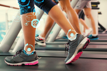 Row of people working out on treadmills against fitness interface