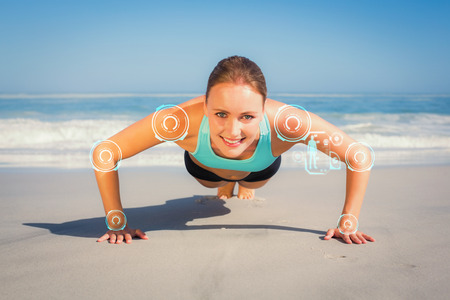 plank position: Fit woman in plank position on the beach against fitness interface