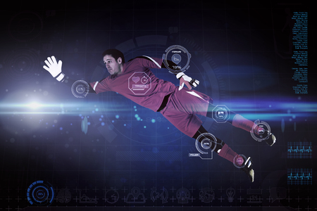 goal keeper: Fit goal keeper jumping up against blue dots on black background Stock Photo