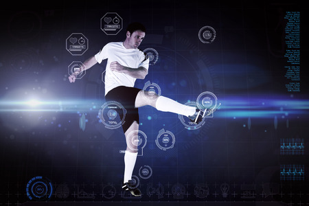 Football player in white kicking against blue dots on black background photo