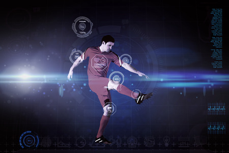 Football player in yellow kicking against blue dots on black background photo