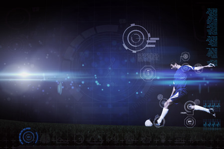 Football player kicking ball against blue dots on black background photo