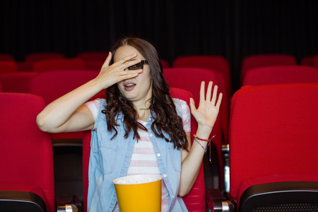 3d film: Young woman watching a scary 3d film at the cinema