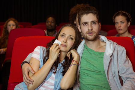 mujer llorando: Joven pareja viendo una película en el cine