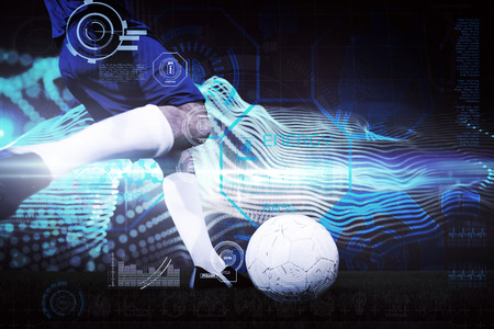 Football player kicking ball against abstract blue glowing black background photo