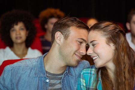 relationship love: Young couple watching a film at the cinema
