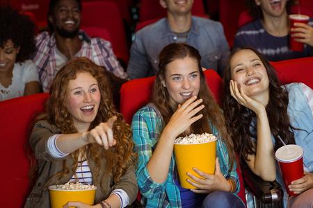 palomitas de maiz: Amigos jovenes que miran una película en el cine