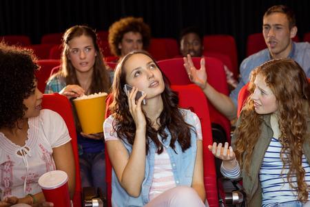 molesto: Mujer molesta en el tel�fono durante la pel�cula en el cine