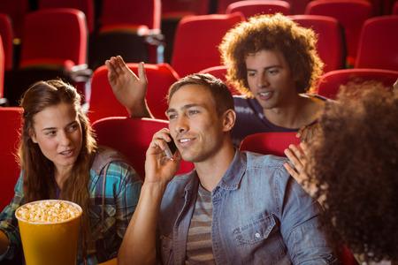 molesto: Molesto hombre en el teléfono durante la película en el cine