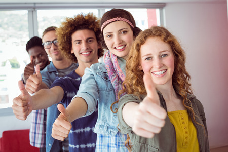 single line: Students smiling in a single line with thumbs up at the college Stock Photo