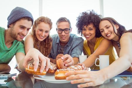 jovenes estudiantes: Estudiantes de moda comer donas en el colegio