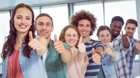 jovenes estudiantes: Estudiantes de moda que muestran los pulgares para arriba en la universidad