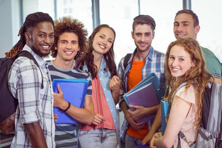 jovenes estudiantes: Estudiantes de moda sonriendo a la cámara junto a la universidad Foto de archivo
