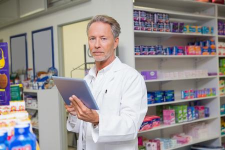 Senior pharmacist using tablet pc in the pharamcy photo